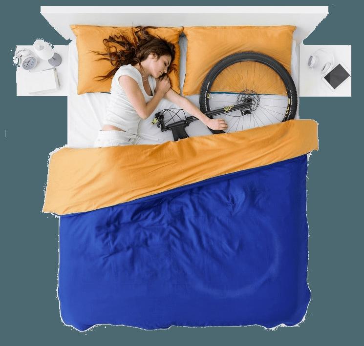 Mulher deitada na cama com uma bike